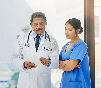 Buy stock photo Shot of a mature doctor and young nurse using a digital tablet together