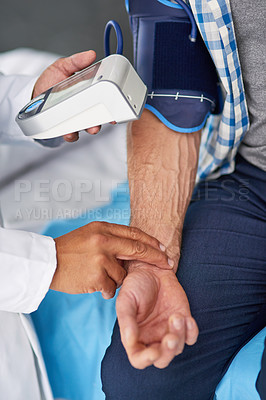 Buy stock photo Cropped shot of a doctor taking a patient's blood pressure reading