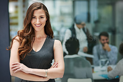 Buy stock photo Portrait of a young businesswoman standing in an office with colleagues in the background
