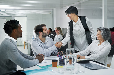 Buy stock photo Cropped shot of businesspeople shaking hands during a meeting in a modern office