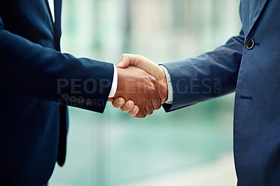 Buy stock photo Cropped shot of two unidentifiable businessmen shaking hands in the office