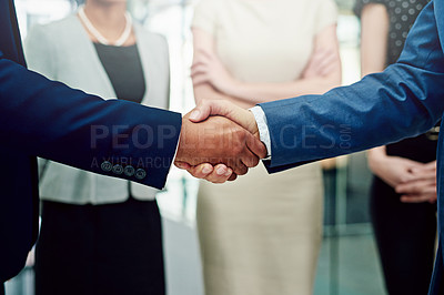 Buy stock photo Cropped shot of two unidentifiable businessmen shaking hands with their female coworkers in the background