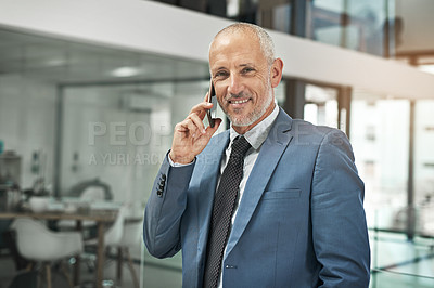 Buy stock photo Portrait of a mature businessman talking on a cellphone in a modern office