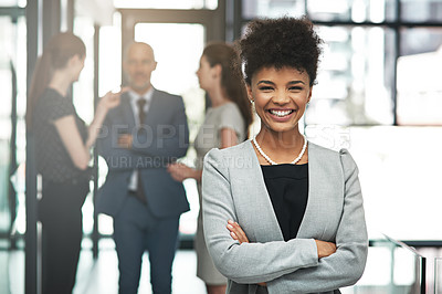 Buy stock photo Portrait of a confident young businesswoman standing in a modern office with colleagues in the background