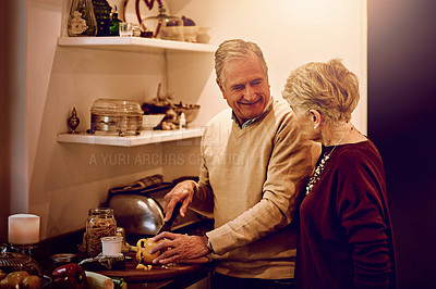 Buy stock photo Cropped shot of an elderly woman watching her husband prepare a meal in their kitchen