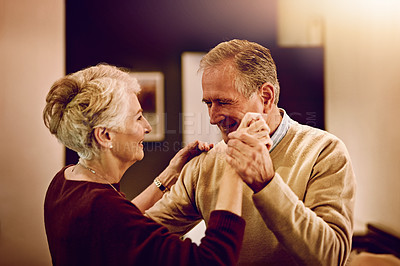 Buy stock photo Shot of an elderly couple dancing with each other in their kitchen