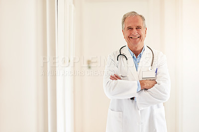 Buy stock photo Portrait of a mature doctor standing with his arms folded and smiling