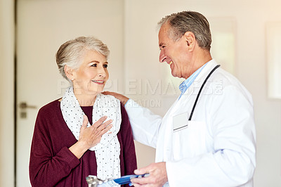 Buy stock photo Shot of a doctor having a conversation with his patient in the clinic