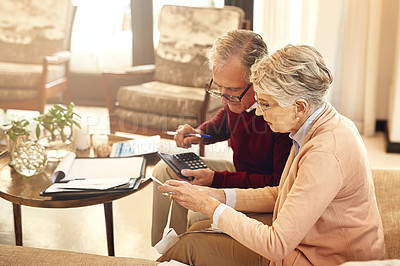 Buy stock photo Shot of an elderly couple working out a budget while sitting on the living room sofa