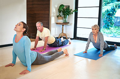 Buy stock photo Shot of a yoga instructor guiding a senior couple in a yoga class