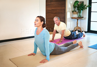 Buy stock photo Shot of a yoga instructor guiding a senior man in a yoga class