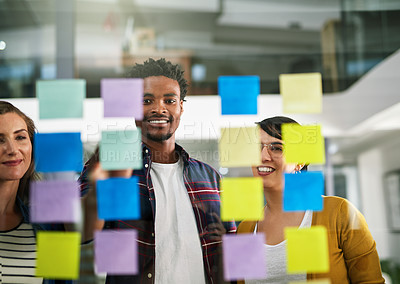 Buy stock photo Cropped shot of coworkers brainstorming using sticky notes on a glass wall in an office