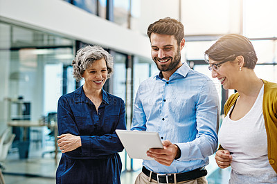 Buy stock photo Cropped shot of a group of creatives working together on a digital tablet in a modern office