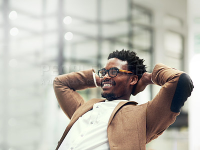 Buy stock photo Cropped shot of a young businessman leaning back in his chair in an office