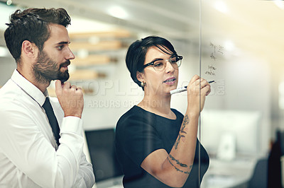 Buy stock photo Cropped shot of businesspeople brainstorming with notes on a glass wall in an office