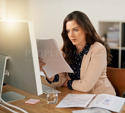 Buy stock photo Cropped shot of a young businesswoman looking through some paperwork in a modern office