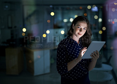 Buy stock photo Portrait of a young businesswoman working late on a digital tablet in an office