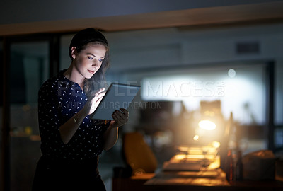 Buy stock photo Cropped shot of a young businesswoman working late on a digital tablet in an office