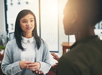 Buy stock photo Cropped shot of two young creatives having a discussion in an office