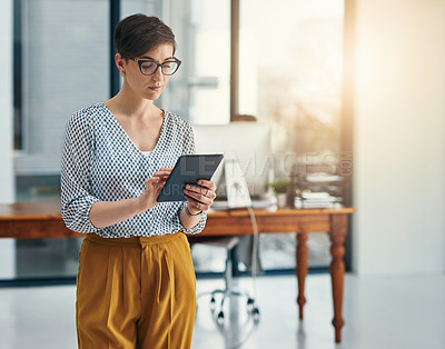 Buy stock photo Cropped shot of a young creative working on a digital tablet in a modern office