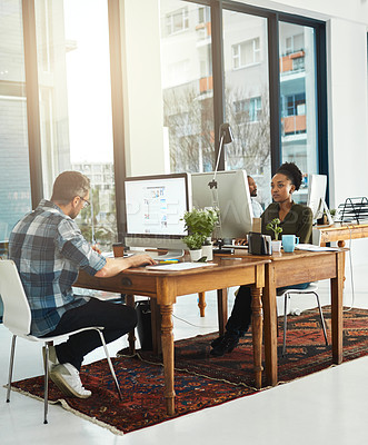 Buy stock photo Full length shot of two businesspeople working on opposite ends of a desk in the office