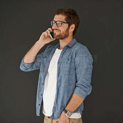 Buy stock photo Studio shot of a young man talking on his cellphone against a grey background
