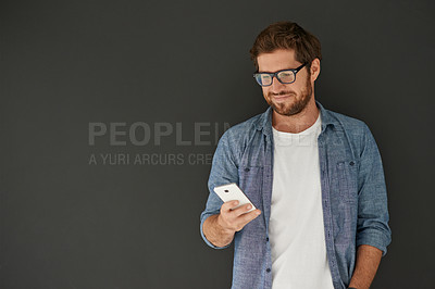 Buy stock photo Studio shot of a young man reading a text message against a grey background