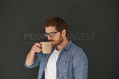 Buy stock photo Studio shot of a young man drinking coffee against a grey background