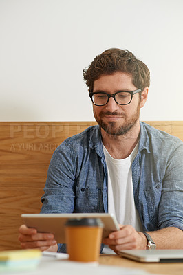 Buy stock photo Cropped shot of a young man working on his digital tablet