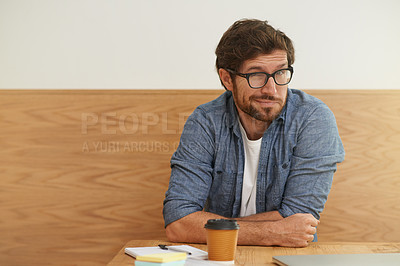 Buy stock photo Cropped portrait of a young man giving you a quizzical look while sitting at a table