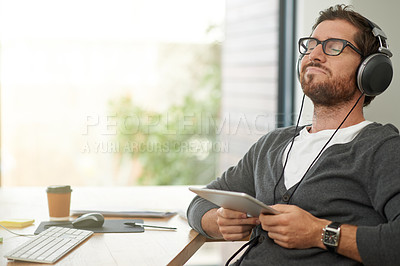 Buy stock photo Shot of a relaxed young entrepreneur using headphones and a digital tablet at his work desk