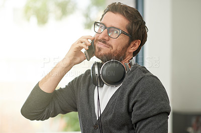 Buy stock photo Shot of a young entrepreneur talking on a mobile phone in his office