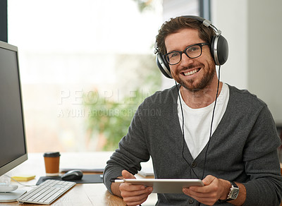 Buy stock photo Portrait of a young entrepreneur using headphones and a digital tablet at his work desk