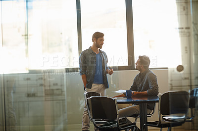 Buy stock photo Shot of a two young businessmen talking together while working in an office