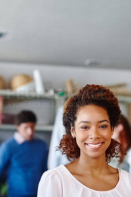 Buy stock photo Portrait of a young fashion designer standing in the workshop while her colleagues work in the background
