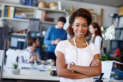 Buy stock photo Portrait of a young fashion designer standing with her arms folded while her colleagues work in the background