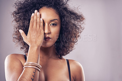 Buy stock photo Portrait of a young woman covering her eye against a plain background