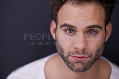 Buy stock photo Studio portrait of a handsome young man posing against a dark background
