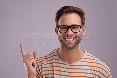 Buy stock photo Studio portrait of a young man pointing towards your copyspace