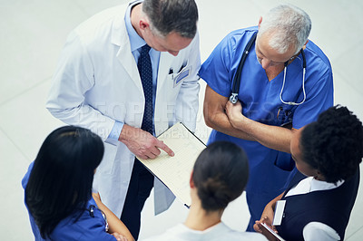 Buy stock photo Shot of a group of doctors talking together over a medical chart while standing in a hospital