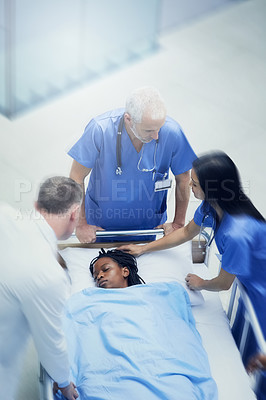 Buy stock photo Shot of a group of medical professionals looking at a patient on a gurney in a hospital corridor