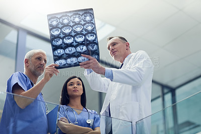 Buy stock photo Shot of a group of doctors looking at a medical scan while standing in a hospital