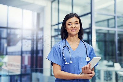 Buy stock photo Portrait of a young female doctor holding a digital tablet while standing in a hospital