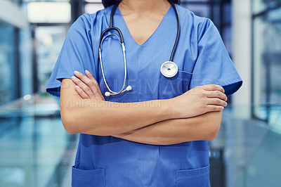 Buy stock photo Portrait of a young female doctor standing with her arms crossed in a hospital