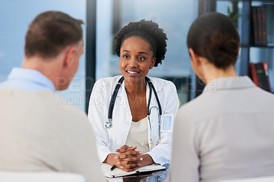 Buy stock photo Cropped shot of a female doctor talking to a married couple in her office