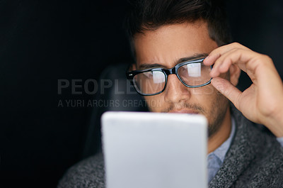 Buy stock photo Shot of a young man wearing glasses using a digital tablet in the dark