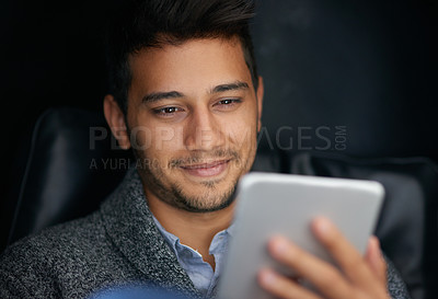 Buy stock photo Shot of a smiling young man using a digital tablet in the dark