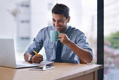 Buy stock photo Shot of a young businessman writing notes and drinking coffee while working on a laptop in an office
