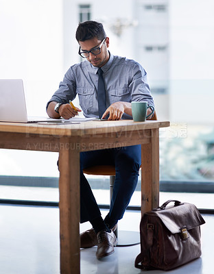 Buy stock photo Shot of a young businessman writing notes while working on a laptop in a modern office
