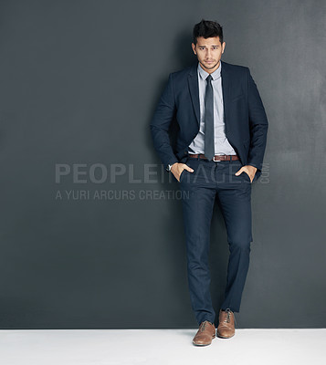 Buy stock photo Studio shot of a young businessman standing with his hands in his pockets against a gray background